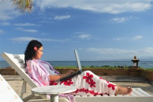 Asian businesswoman working on her vacation at the beach